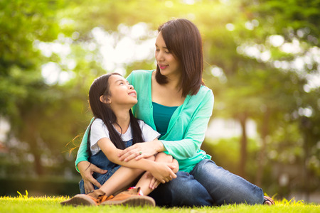 daughter mother: Happy young mother with her daughter at park Stock Photo