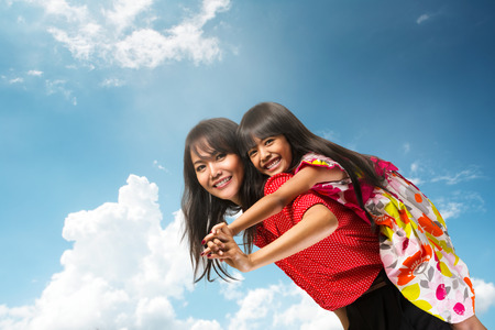 Happy asian mother piggyback ride her daughter over blue sky Фото со стока