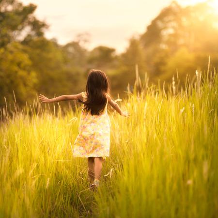 jolie petite fille: Petite fille exécutant sur le pré avec le coucher du soleil