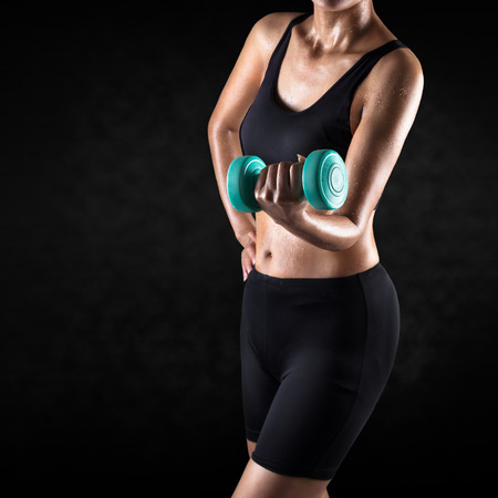 asian abs: Athletic woman lifting dumbbell select focus at dumbbell, Isolated over grey background Stock Photo