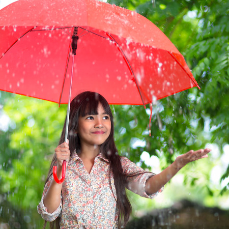 lluvia paraguas: Pequeña muchacha asiática con el paraguas en la lluvia Foto de archivo