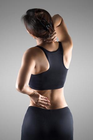 osteoporosis: Mujer con dolor de espalda dolor y dolor de cuello, aislado sobre fondo gris