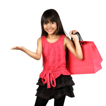 Smiling little asian girl hand up showing empty space on her hand with shopping bags, Isolated over white photo