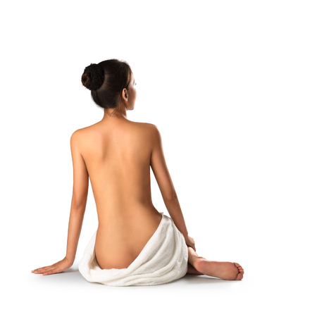 Asian woman wearing towel sitting on the floor back view, Isolated over white photo