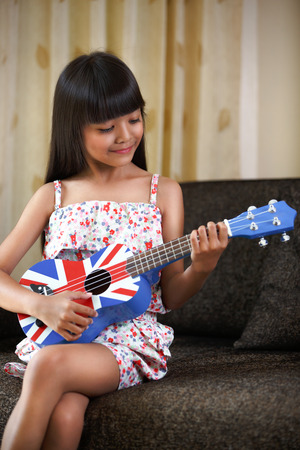 playing music: Pretty little asian girl playing the guitar at home