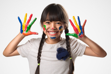 Little asian girl with her hands in the paint, Isolated over white photo