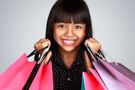 Closeup smiling little asian girl holding shopping bags, Isolated on grey photo