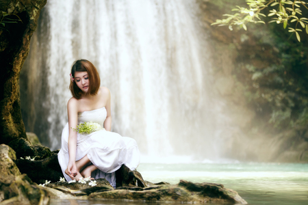 Young woman relaxing in water stream near waterfall photo