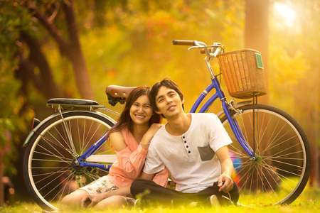asian adult: Young asian couple sitting on ground in park relaxing, Outdoor portrait