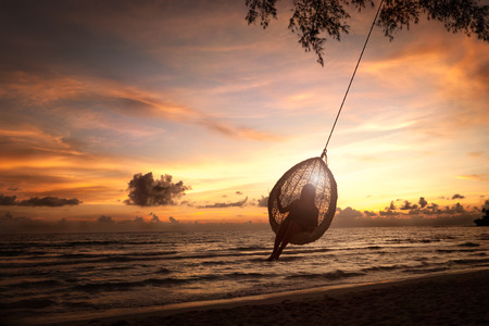 koh: Silhouette woman on a beach swing