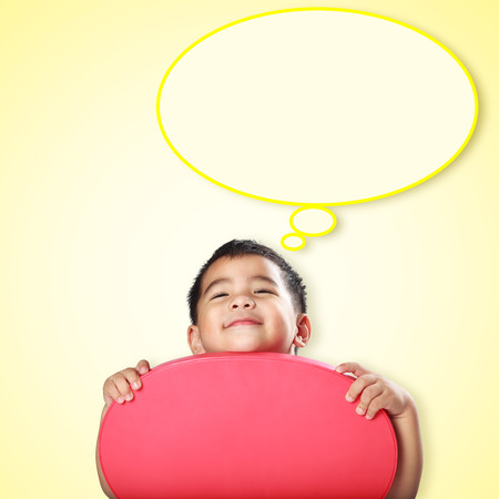 Smile little asian boy with empty think bubble on yellow background photo