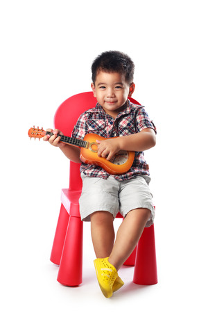 sits on a chair: Little asian boy sits on a chair with a guitar, Isolated over white