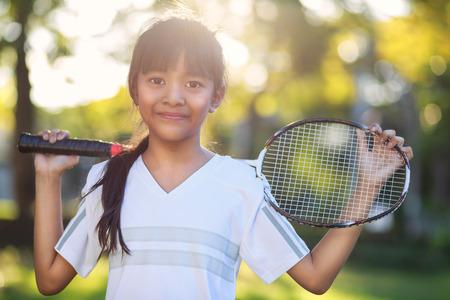 Closeup cute little asian girl holding a badminton racket, Outdoor photo