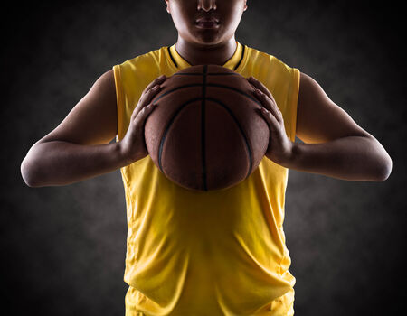 Teenager boy holding a basket ball, Isolated on-a black