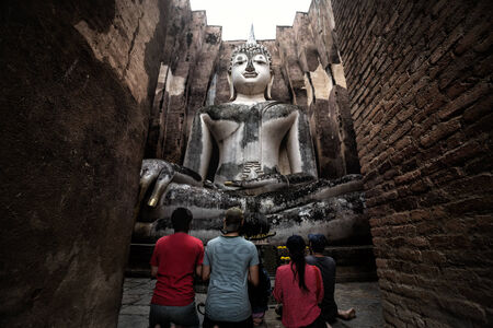 Asian family pay respect to the big buddha at srichum temple, Sukhothai thailand photo