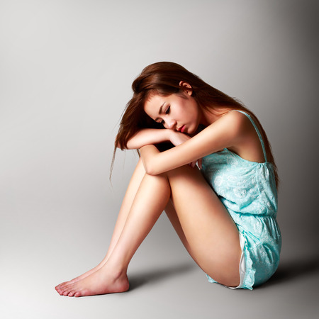 Sad pretty girl sitting on the floor, Isolated over grey background Stock Photo