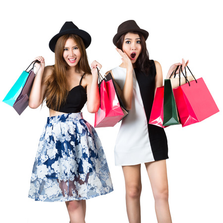 Beautiful asian teen girls carrying shopping bags, Isolated over white photo