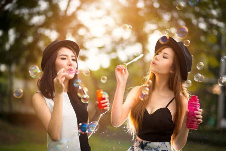 Beautiful asian teen girls blowing soap bubbles, Outdoor portrait photo