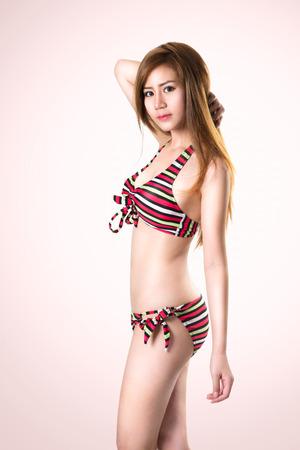 Pretty swimsuit fashion young asian woman posing photo