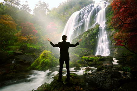 Relaxing businessman standing at waterfall, Success in business concept photo