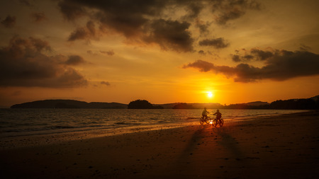 Children playing on the beach at the sunset photo