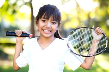 tennis racket: Primer linda niña asiática con una raqueta de bádminton, al aire libre