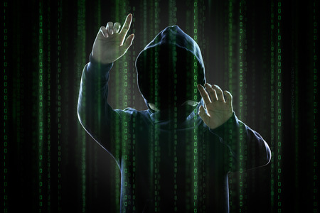 Faceless hooded anonymous computer hacker with programming digital code from monitor