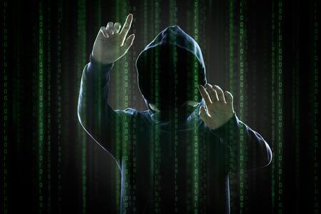 Gezichtsloze hooded anonieme computer hacker met het programmeren digitale code van de monitor