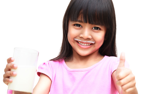 Smiling little girl with a glass of milk, Isolated over white