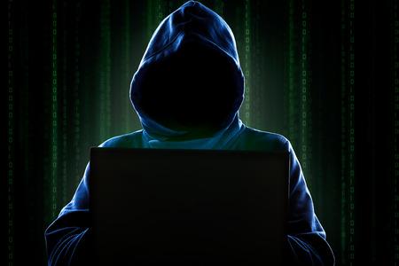 virus informatico: Faceless hacker an�nimo con capucha con la programaci�n de c�digo digital de pantalla