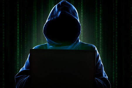 computer crime: Faceless hooded anonymous computer hacker with programming digital code from monitor