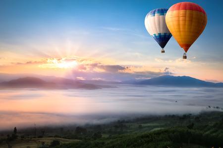 Hete luchtballon over zee van mist Stockfoto