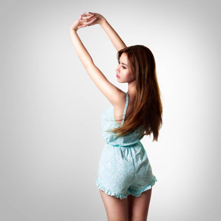 Back view of young asian woman in sleeping dress standing relaxed with hand over, Isolated on grey background photo