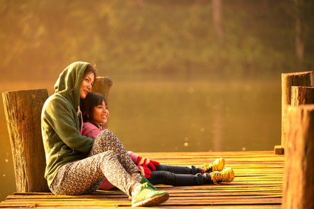 two girls hugging: Mother and daughter sitting on the wooden bridge near the river