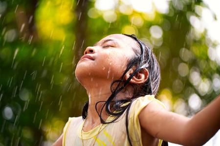 bambini: Primo piano poco ragazza asiatica sotto la pioggia d'estate