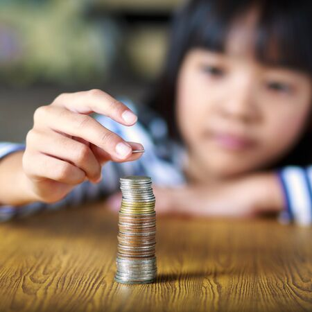 investment ideas: Little girl counts his coins on a table, Select focus at coins Stock Photo