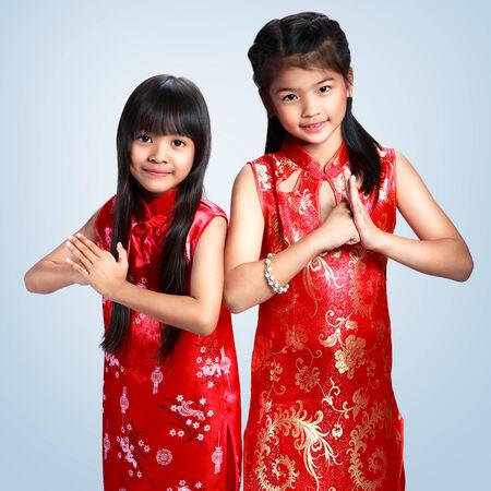 niños chinos: Dos niña feliz asiático que desean un feliz año nuevo chino con cheongsam tradicional de pie, aislado sobre fondo gris