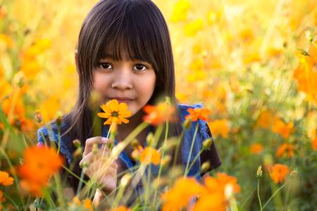 Little asian girl on the flower field photo