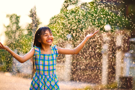 rain water: Happy little asian girl in the summer rain