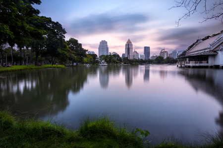 Business district cityscape from a park with twilight time from lumpini park, Bangkok Thailand photo