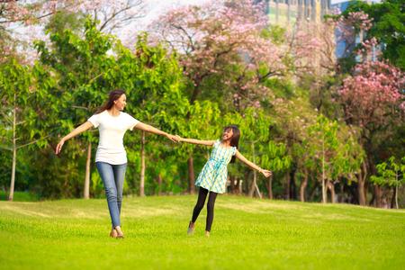 mama e hija: Feliz madre de familia y del niño pequeño hija corriendo y jugando en el parque