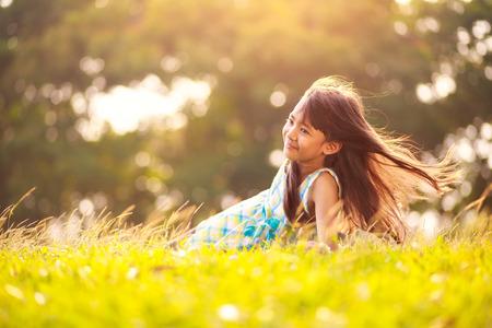 Nettes kleines asiatisches Mädchen mit in das Gras an einem sonnigen Sommertag, Outdoor-Porträt