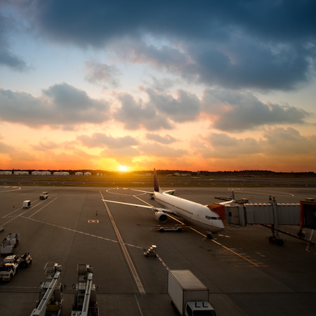 Airplane near the terminal in an airport at the sunset photo