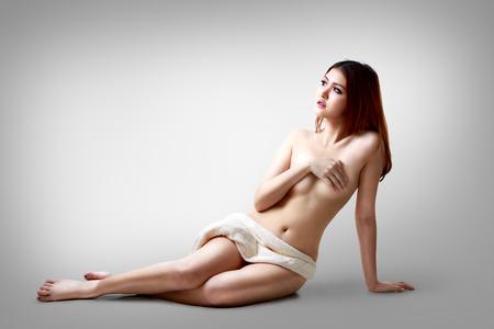 nackte schwarze frau: Reizvolle asiatische Frau sitzt auf dem Boden, isoliert auf grauem Hintergrund