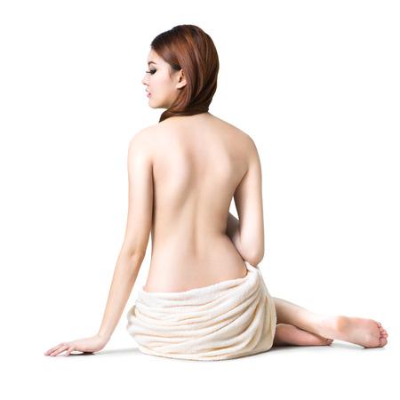 seins nus: Asian femme portant une serviette assis sur le sol vue de dos, isolé sur blanc