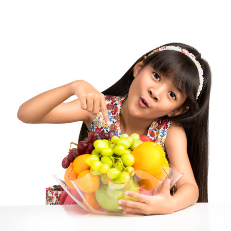 Happy little asian girl sitting on the table with plate of fruit, Isolated over white photo