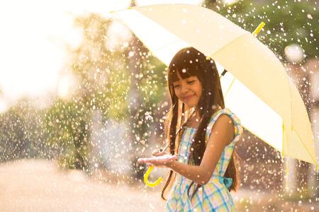 lluvia paraguas: Bastante joven muchacha asiática en la lluvia con paraguas
