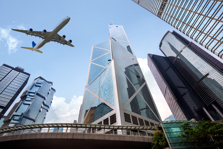 hong kong street: Tall city buildings and a plane flying overhead, Hong Kong Stock Photo