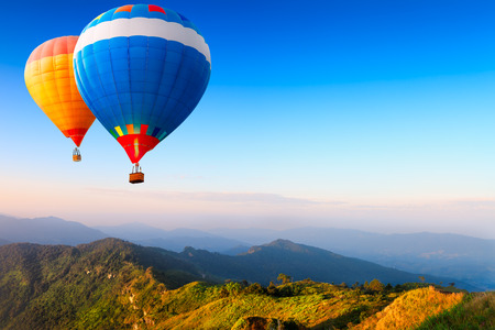 hotair: Colorful hot-air balloons flying over the mountain Stock Photo