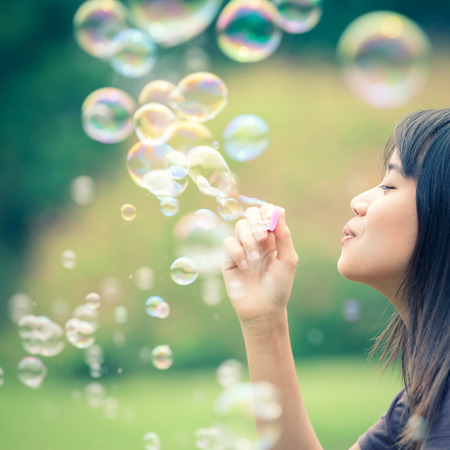 woman blowing: Teenager asian girl with soap bubbles in the park, Cross process colour tone